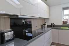 high gloss slab modern kitchen with Neff induction hob built and grey quartz granite silestone worktop with oak laminate panel and black glass splashback. Kitchen Island Decor, Granite Kitchen, New Kitchen, Kitchen Ideas, Grey Gloss Kitchen, Black And Grey Kitchen, Kitchen Diner Lounge, Diy Kitchen Accessories, Grey Kitchens
