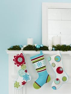 A simple mantel arrangement complements whimsical Christmas stockings. Draw some colors from your stockings into the mantel for a cohesive look. Here, colorful ornaments, white candles and evergreen garland complete the display.