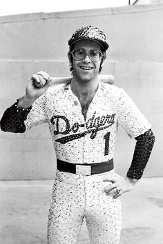 English singer and songwriter Elton John poses in Bob Mackie's now famous sequined white Dodgers uniform at Dodger Stadium in Los Angeles, October