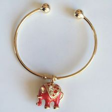 Gold plated bangle bracelet with balls on ends and dangling red ename... Lot 937