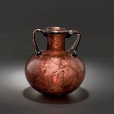 Roman Glass Aryballos with a Cylindrical Neck                                                                                                                                                        Culture :                  Roman, Roman Imperial                                              Period : 1st century A.D.                                          Material : Aubergine glass: