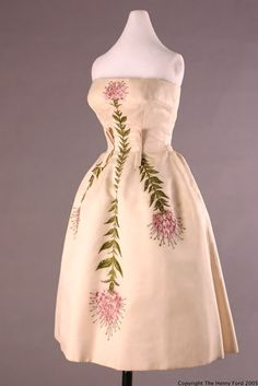 Ivory cocktail Dress (circa 1957).  Strapless, fitted bodice with full skirt.  The body of the fabric and a crinoline petticoat gives the skirt a nice full 'bell' shape.  The detailing of thistles is beautiful embroidered and accented with crystal beadings