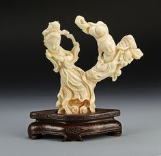 China, carved coral lady statue, with two intertwining figures, intricately carved, with flowing robes, floral motifs, and wood base with gilt details. Height 6 in.