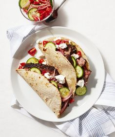Quick pickled onions (just let them sit in vinegar for five minutes) are tossed with chopped Persian cucumbers, sliced grape tomatoes, and seasonings to create a topping that's bursting with fresh summer flavors. Spiced steak and crumbled Feta complete the part Greek, part Mexican meal.