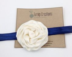 So simple & sweet!  A navy headband featuring a single soft satin rolled flower in a beautiful cream color. The back of the headband is finished with
