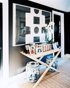X-base console with garden stools and framed family photographs