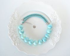 This simple, yet stunning necklace is made up of turquoise satin cord and turquoise ceramic beads. You can wear it during the day, the evening, winter or