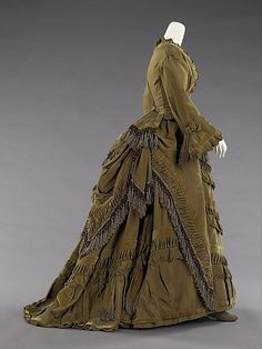 c1875 bustle silhouette dress of silk, cotton and glass - (side view). A back view of this dress can be seen at http://www.metmuseum.org/collections/search-the-collections/80094026?img=2