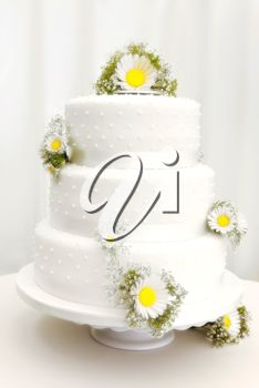 iPHOTOS.com - Photo of a traditional three tier wedding cake with daisy flower decorations.