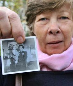 """""""Violette Wallenborn holds a picture of herself in the arms of her Nazi father.  This article is about the Lebensborn children -- children with Aryan qualities Nazis raised as their own -- reclaiming their roots."""""""