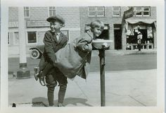 SIBLINGS: Brother helps younger sister to a drink of water, ca. 1900s