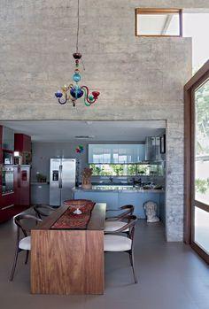 Sala de jantar | A cozinha fica no bloco de concreto e é aberta para o living. Os armários da Florense têmacabamento de laca brilhante em contraste com o piso de porcelanato, que imita cimento (Foto: Fotos e produção Projeto Sertões)