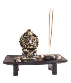 A beautiful and divine piece; this is a perfect addition to your home this festive season. It is a ganesha statue in Golden Rusty finish placed on a wooden tray. Flanked with a stone agarbati holder. Accompanied by more stones that enhance its beauty.