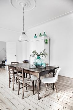 Beautiful Copenhagen apartment full of white, peaceful, rustic spaces! The rustic wooden floor in this dining room is complimented with the green glass tableware! #white #wood #rustic #scandi
