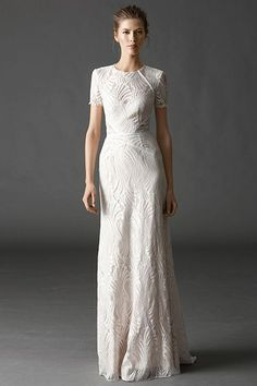 Between the exposed back, the illusion neckline, and the flowing design, this short-sleeve sheath was made for modern brides. But, the best part? The lacey, subtle cutouts at the waist that add a bit of drama.
