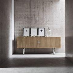 murs en béton, commode moderne en bois clair et cadres de photos en noir et…