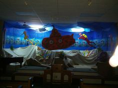 Our transformed stage for vbs submerged 2016.  The submarine, seahorse and scuba diver are hanging from the ceiling and made out of the vinyl corrugated board that candidate signs are made from.