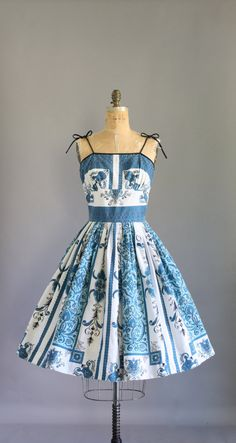 Vintage 50s blue and turquoise floral border print dress. Shelf bust. Spaghetti straps tie to adjust fit. Metal zipper up back. Full skirt.