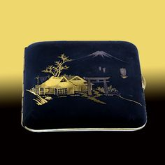 Damascene Japanese Cigarette Case  This lovely damascene cigarette case depicts a rustic piece of Japanese landscape. A Shinto shrine, marked by a characteristic gate, sits in the foreground; a mountain rises behind it. The piece, which dates to the early twentieth century, was most likely purchased as a souvenir during a holy pilgrimage.  3 1/4 X 3 1/2 inches.