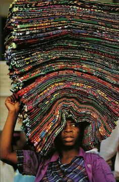 Africa | A vendor peddling wax prints in Lome, Togo | Image taken from National Geographic, June 1994. Photographer unknown