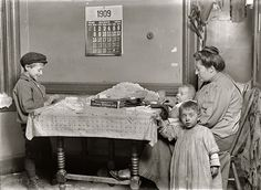 Woman rolling papers for cigarettes in a New York tenement. 1909.