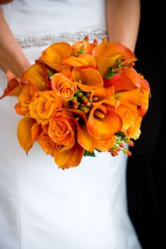 Roses, callas, and hypericum in this bright monochromatic bouquet