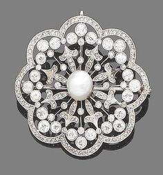 A diamond and pearl brooch/pendant, 1905 The 9.1mm. bouton pearl, within a finely pierced old brilliant, single and rose-cut diamond surround, old brilliant and single-cut diamonds approx. 3.25ct. total, pearl remains untested, diameter 4.9cm.