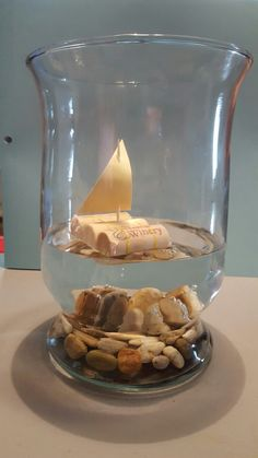 Cork boats! Centerpieces for my wedding!  3 corks 2 Ouchless rubber bands 1 Toothpick Paper Rocks in the bottomof a vase with water  Super easy and REALLY cheap!