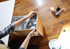 A partir do centro, deite cuidadosamente a foto no lugar, alisando como você vai. Tente evitar bolhas de ar ou rugas no papel como você trabalha e suavizar ou para fora para os lados ou para cima ou para baixo, conforme necessário. Repetir do outro lado e continuar o processo em todas as gavetas.