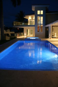 """Iridescent glass tile pool & spa with inserts of fluorescent glass tile which glows at night for up to seven hours. Travertine coping with a 2"""" vertical drop down and flush with glass tile. Very modern, clean and elegant."""
