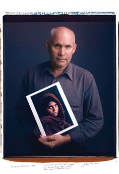 "Steve McCurry holds his 1984 photo of a young woman from Peshawar, Pakistan. ""I looked for this girl for 17 years and finally found her in 2002. Her name is Sharbat Gula."" 