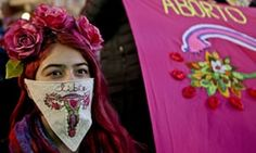 "A woman wearing a handkerchief embroidered with a uterus and the Spanish word for ""free"" participates in a pro-abortion march in Santiago, Chile"