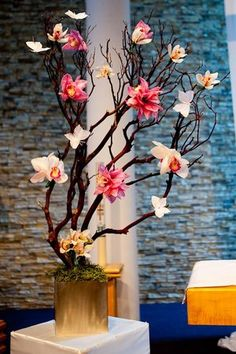 Blush pink cymbidium orchids and bright and pale pink flowers on manzanita branches