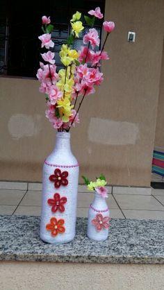 Garrafas de vidro cobertas com lã branca, adesivo de pérolas e flores em quilling.