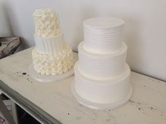 Two, three tiered butter cream wedding cakes showing neat, swirled and rosette design