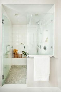 Luxurious white shower with frameless glass door