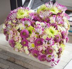 composition florale originale avec des gerberas roses et verts en forme de cœur