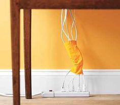 Corral Cords and Eliminate Clutter - With all the extra socks I have lying around here, this is a great idea for keeping cord clutter organized. Organisation Hacks, Cord Organization, Genealogy Organization, Organize Your Life, Organize Cords, Do It Yourself Design, Ideas Geniales, New Uses, Real Simple