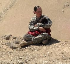 19 year-old US Army PFC Rachel Winner, 4th Squadron, 6th Air Cavalry Regiment, with a sleeping 4 year-old motherless Iraqi girl.The girl was one of the children attending a pediatric clinic on the base