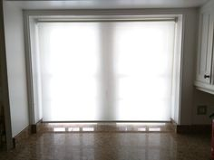 Sheer roller blind with white gloss bottom bar installed in kitchen in Chelsea. http://www.theblindshop.com