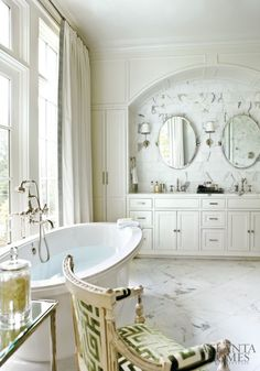 White neoclassical bathroom with oversized soaking tub and grecian print chair. Marble tiles.  Source: French Style Authority