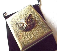 Metal cigarette case with an owl as it's centerpiece.