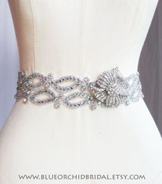 Double-wave crystal pattern sash with removeable brooch.  Design & Image by Blue Orchid Bridal (www.blueorchidbridal.etsy.com)