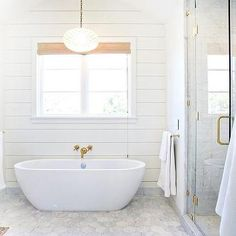 Serena & Lily Capiz Scalloped Chandelier elegantly hanging above an egg shaped bathtub in a cottage bathroom designed with shiplap walls and large marble hexagon floor tiles. Grey Floral Wallpaper, Scallop Tiles, Bathroom Chandelier, Grey Floor Tiles, Small Hallways, Transitional Bathroom, Ship Lap Walls, Blue Bedroom, Bathroom Interior
