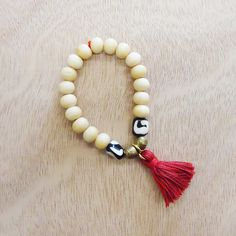 RED TASSEL // made with carved bone beads with handmade Ethiopian brass accent beads by Congolese refuge women // www.gaiaforwomen.com