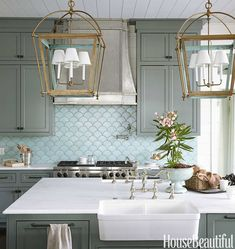Coastal style kitchen with large, latern like lights and carrara marble counter tops