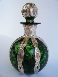 Green art glass perfume bottle with Art Nouveau silver overlay. Elegant.