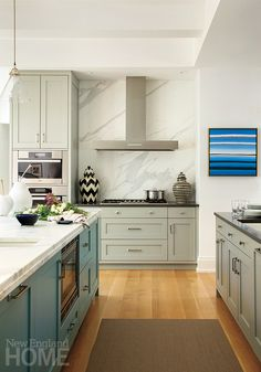 The home's gray and blue palette is enhanced in the kitchen with white Calacatta marble.