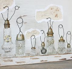 Salt and pepper shakers as name card holders or labeling food. Easy to find in thrift stores, easy to embellish with some fake jewelry bling. Seriously love this!