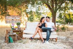 White couch under a tree with crate end tables were used for this styled engagement session